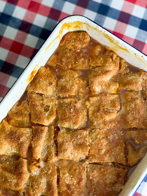 Peach Dumpling Cobbler, a cobbler made with fresh sliced peaches layered between three layers of sweet, tender, buttery dough.  Boiling water is poured over the whole cobbler, where all the magic happens.  The dough transforms, making sheets of dumplings.