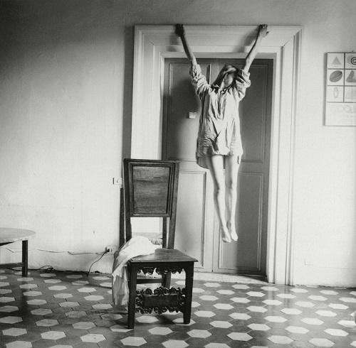 Foto cool: una joven levita y se sostiene del marco de la puerta de una habitacion. Ella pareciera estar bailando un hermoso ballet.