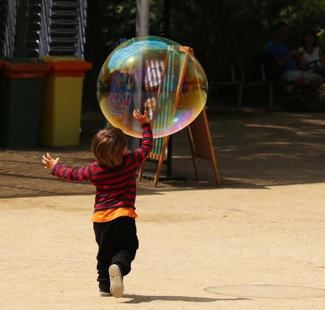 Kind rennt riesiger Seifenblase hinterher