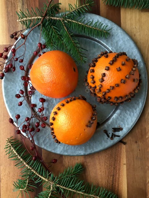 How to make pomanders: oranges studded with whole cloves. They have an old fashioned charm to them and a lovely scent that will last beyond the holiday season.