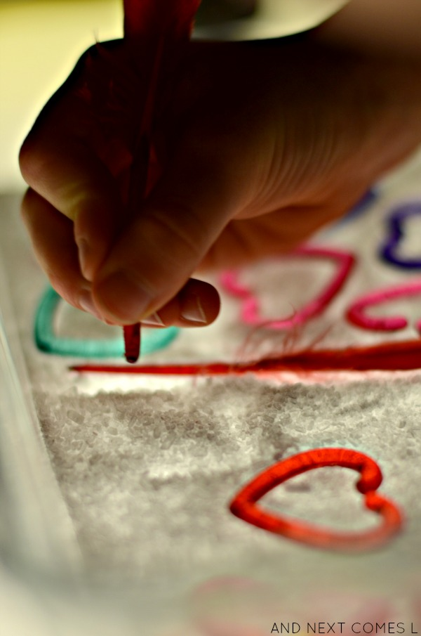 Writing in a Valentine's salt tray on the light table