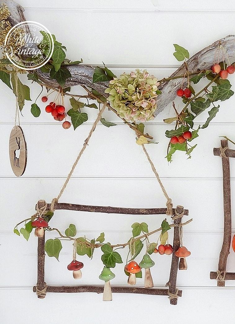 Bilderrahmen aus Haselzweigen geschmückt mit Herbstfrüchten.