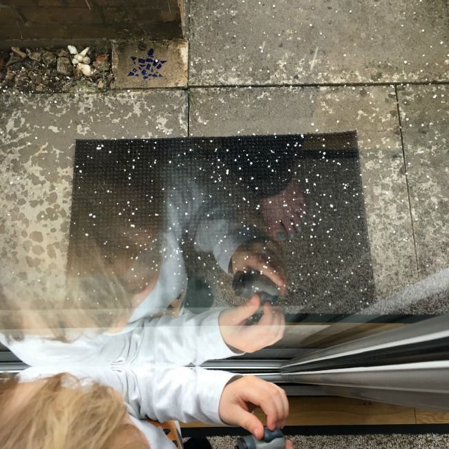 toddler and reflection looking out window at hail hitting mat