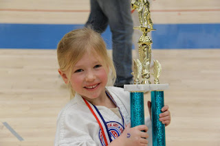 A young karate girl holing her trophy from karate classes