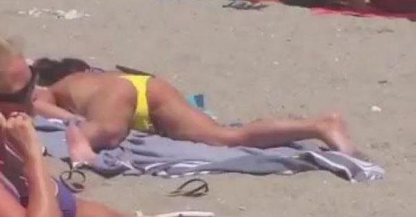 Cette femme seins nus surprise en train de se toucher sur une plage bondée sans se soucier des autres vacanciers autour d'elle !