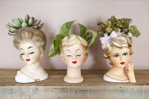 trio of vintage lady head vases containing plants