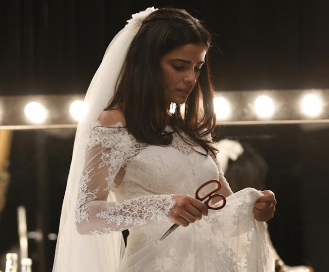 toia vestida de noiva em seu primeiro casamento olhando para o vestido com uma tesoura na mao