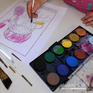 a child painting a coloring page of a jellyfish