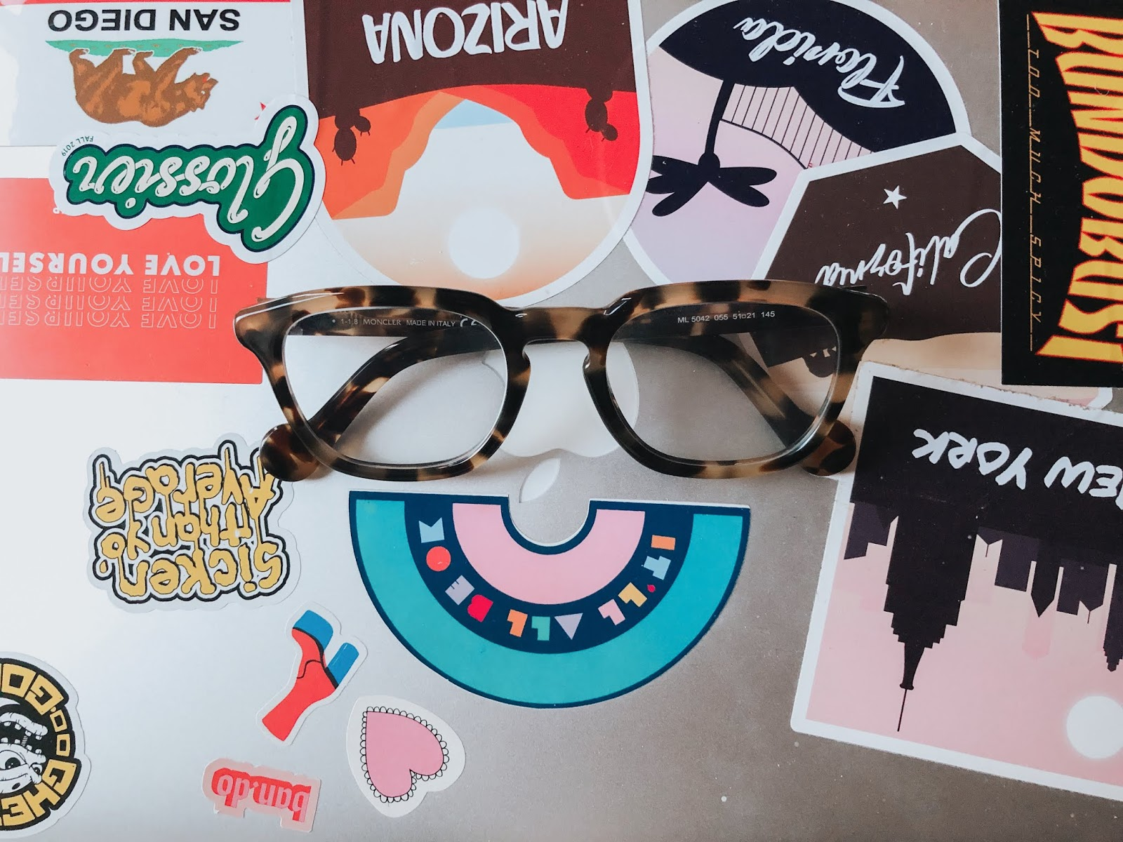 pair of tortoiseshell glasses on top of sticker covered laptop
