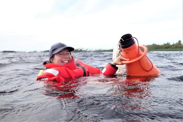 Iloinen kartoittaja kelluu vedessä pelastautumispuvussa vesikiikarin kanssa.