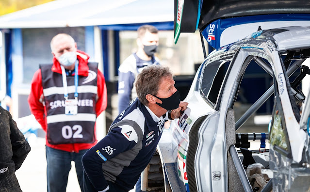 Malcolm Wilson inspecting crashed Ford Fiesta WRC car