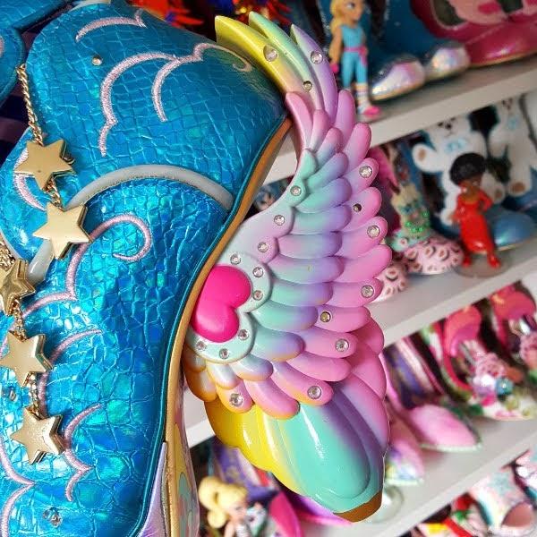 rainbow winged heel of shoe in front of shoe shelves