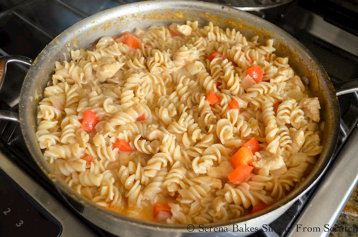 Cooked Chicken and Pasta with Bell Pepper in a stainless steel pan.