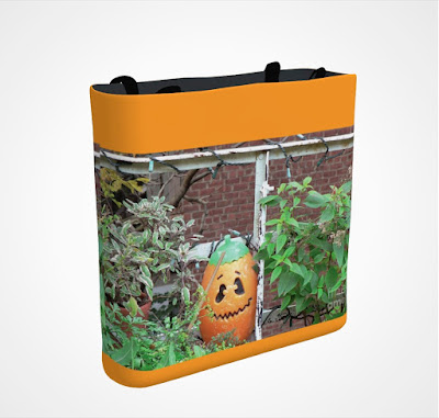 "This screen-shot features an orange tote/bag/pouch bag that has an image that was taken in my garden when it was decorated for Halloween. It is a picture of a Jack-O-Lantern ""standing"" beside red flowers. The tote/bag/pouch is available in three sizes (13"" by 13"", 16"" by 16"" and 18"" by 18""). It is available for purchasing via Fine Art America @ https://fineartamerica.com/featured/all-hallows-eve-patricia-youngquist.html?product=tote-bag-13-13"