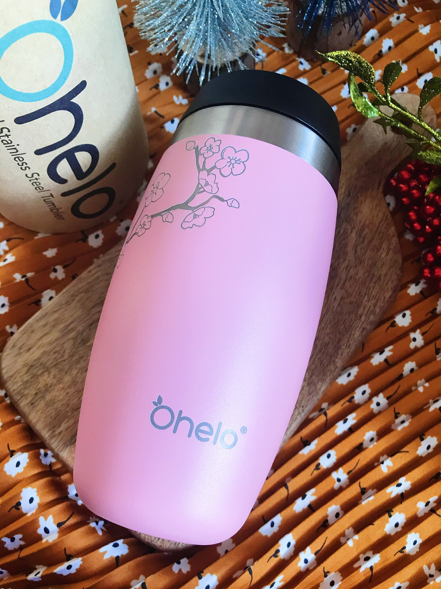 Ohelo Pink Blossom Travel Cup on wooden chopping board, on orange scarf as background