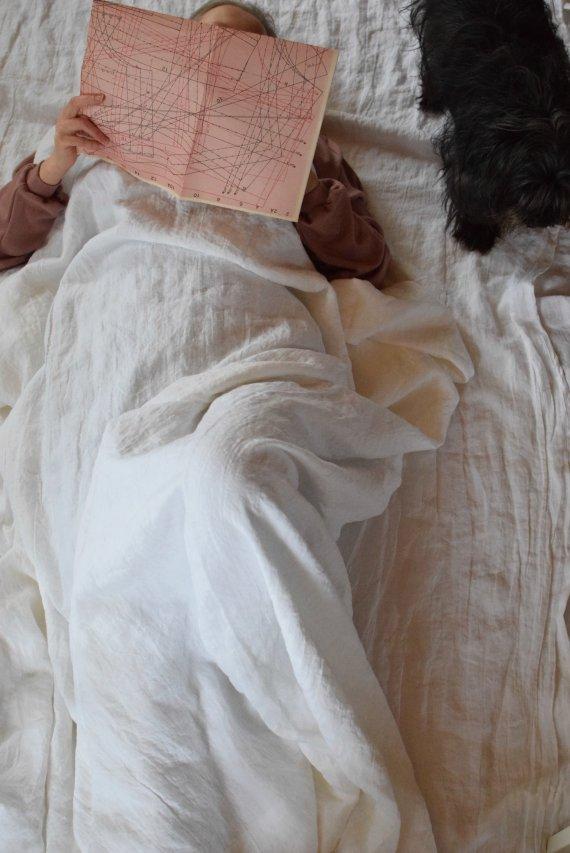 Naineen lojuu koiran kanssa sängyllä ja lukee kaava-arkkia.