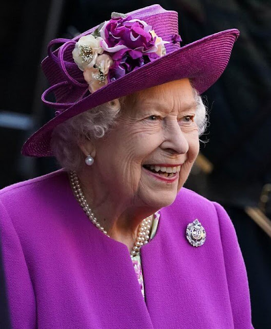 The Queen wore a floral print dress and purple coat and purple hat. diamond brooch