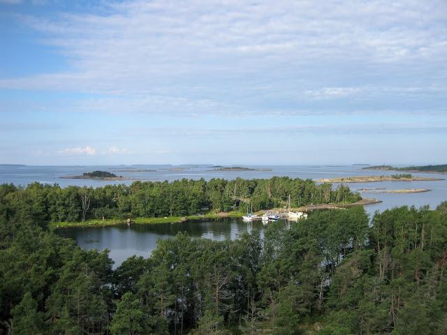 Korkealta otettu kuva. Lahti, jossa näkyy veneitä laiturissa. Taustalla merta ja pieniä luotoja.