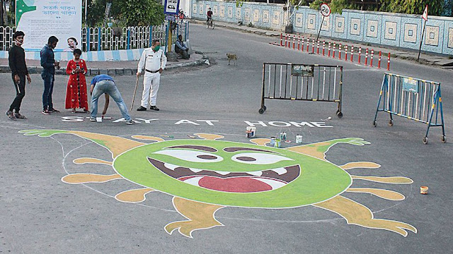 Artists draw graffiti on a road at Airview More in Siliguri on Friday to create awareness of the coronavirus