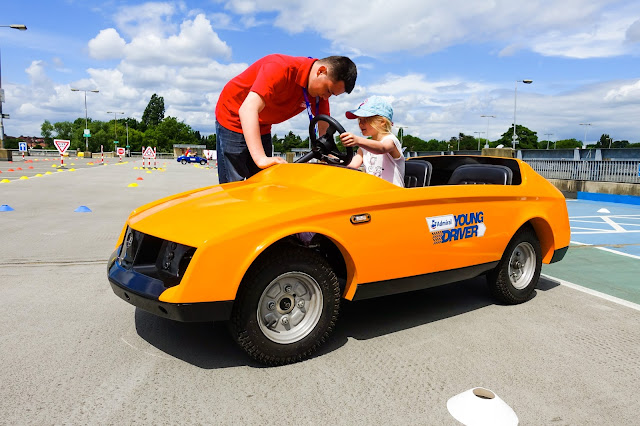 My daughter sitting in an orange, two seater, open topped firefly car with an instructor showing her how to drive it, on the roof of Brent Cross shopping centre car park