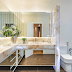 Banheiro com banheira e bancada de canto em ônix iluminado com cuba dupla esculpida!
