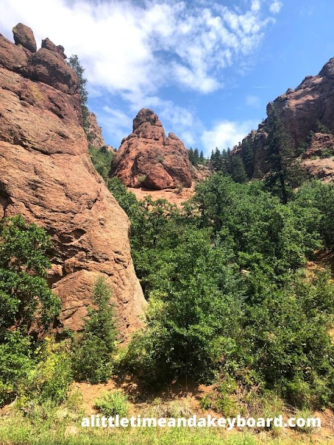 Contrast of reddish rocky landscape and soft green hues of evergreens at North Cheyenne Canon Park in Colorado Springs
