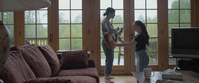 Anna teaches Beth how to play guitar