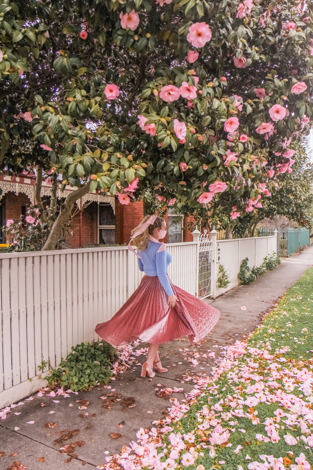 Liana stands beneath a heavily laden tree full of pink flowers. She wears pink velvet heels, a pleated pink velvet skirt, a cropped and fitted blue sweater. She also has on a pretty pink linen mask which ties with a bow that drapes either side of her ponytail