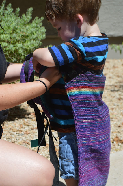 Image of hands of fair skin woman placing shoulder straps of purple rainbow Onbu under the arms of fair skin brown haired toddler