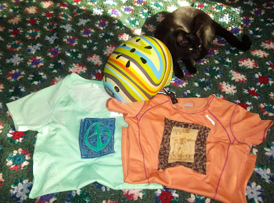 A black cat, Miss Starfire, reclines behind a bicycle helmet, patterned in swirls of green, yellow and brown, that has been positioned atop two folded sports jerseys. The left jersey, a mint-green v-neck, is decorated with a green peace symbol aplique sewn onto a peace of worn blue floral brocade fabric. The orange scoop-necked jersey on the right is decorated with a piece of mustard-yellow on mustard-yellow embroidery inside a 'picture frame' of patterned fabric, light-brown leaves against a darker shade of brown.