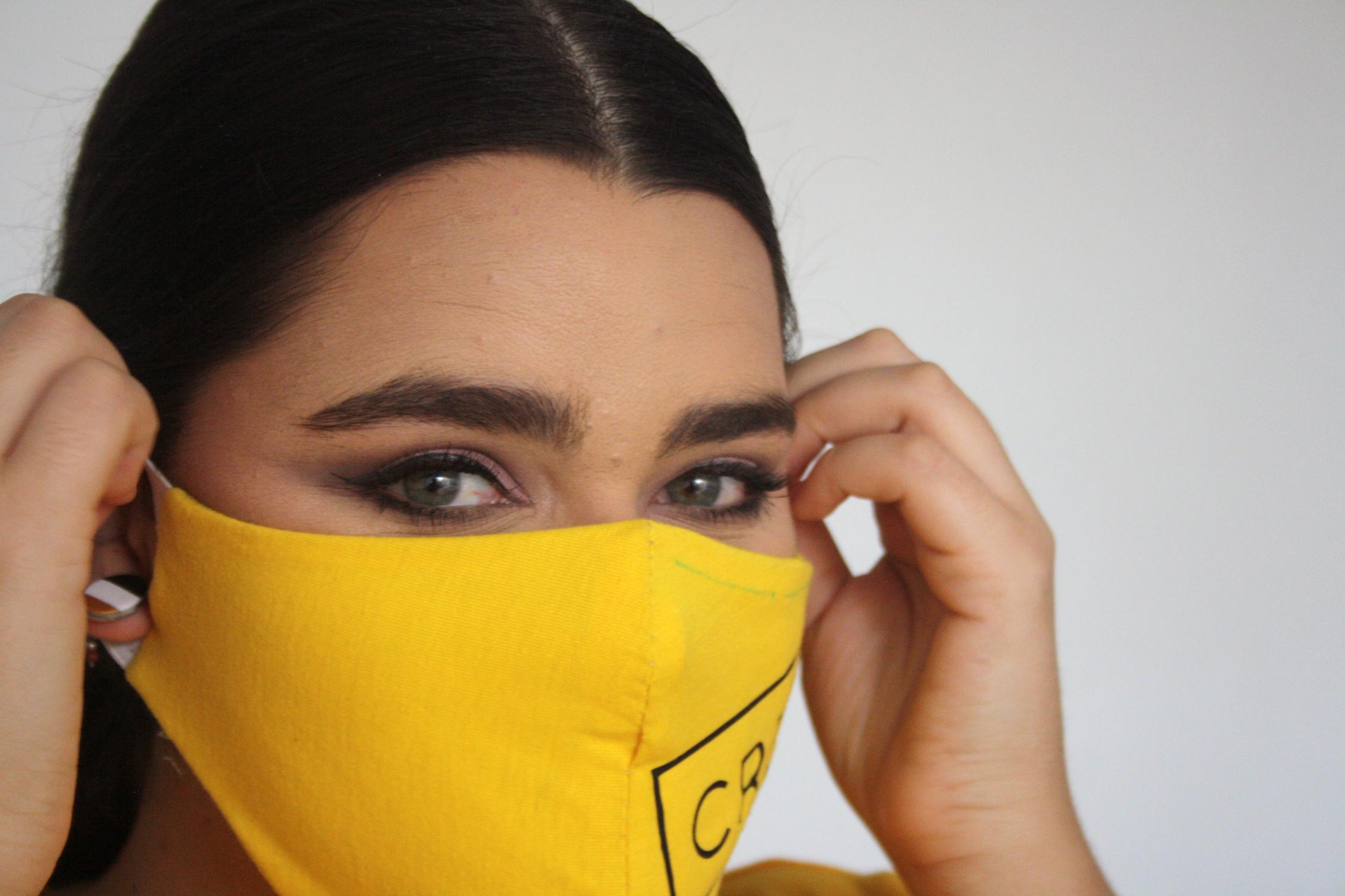 En la foto una mujer usa una Minkarillas de tela amarilla