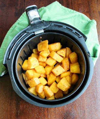 air fryer basket with roasted butternut squash cubes in it