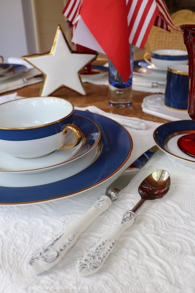 Labor Day patriotic French Country table setting with white Matelasse place mats and white scroll flatware