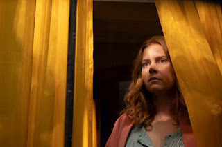 Amy Adams looking out a window through yellow curtains