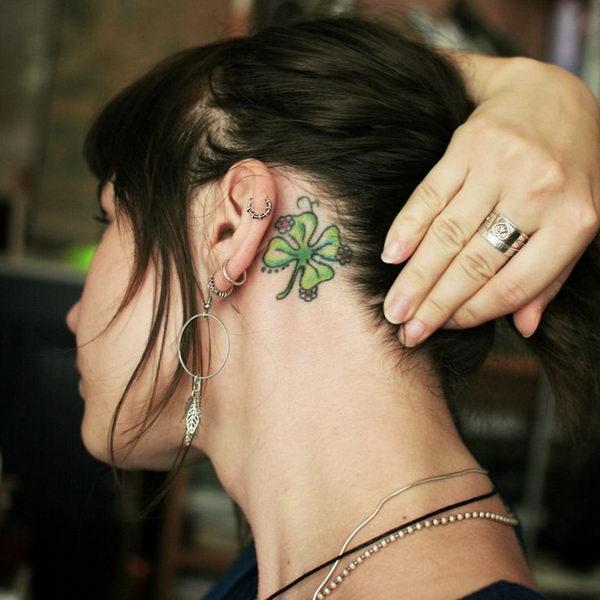 chica morena se recoge el cabello, detras de la oreja vemos el tatuaje de un trebol