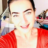 Mulher, de olhos claros, vestindo vermelho