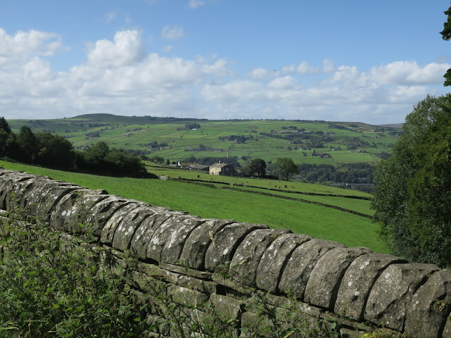 Looking over dry stone wall towards house in West Yorkshire countryside.