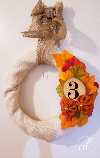 DIY fall wreath using burlap and artificial fall leaves. Use a wood slice for apartment or house number.