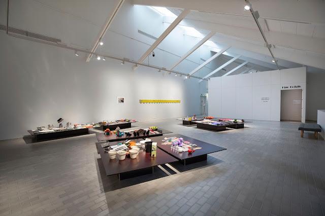 Kouvolan taidemuseo Poikilon yläkerran näyttelytilaan vaneritasojen päälle koottuja esinekoosteita, jotka taiteilija Timo P. Vartiainen on kerännyt roska-astioista ja roskalavoilta.]