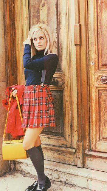Alejandra Colomera vestida con jersey azul, falda roja cuadros escoceses, tirantes en color gris, calcetas gris y zapatos estilo colegial negro