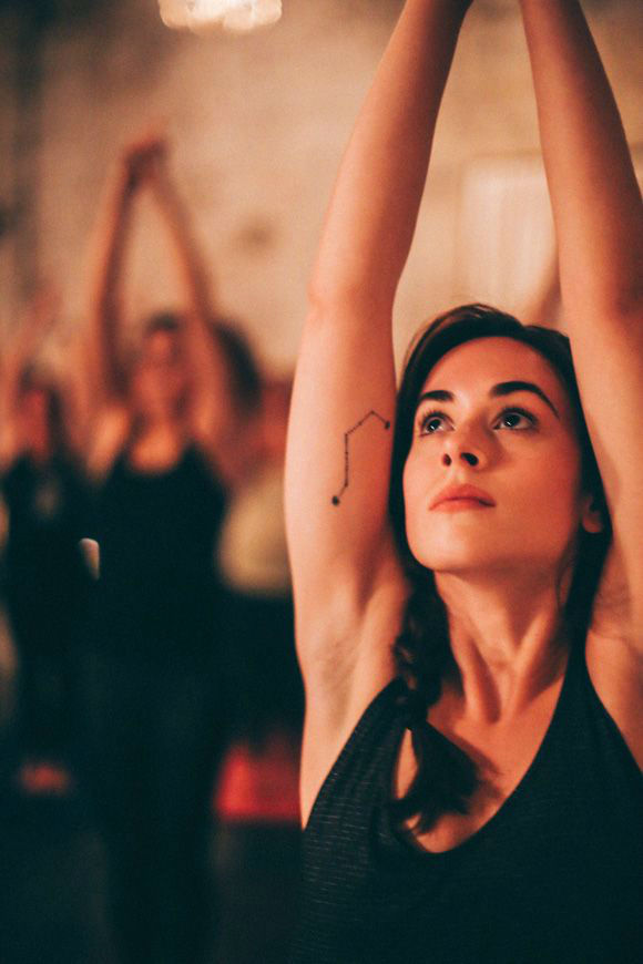 actriz bailando, levanta los brazos y vemos en uno de ellos el tatuaje de una constelacion