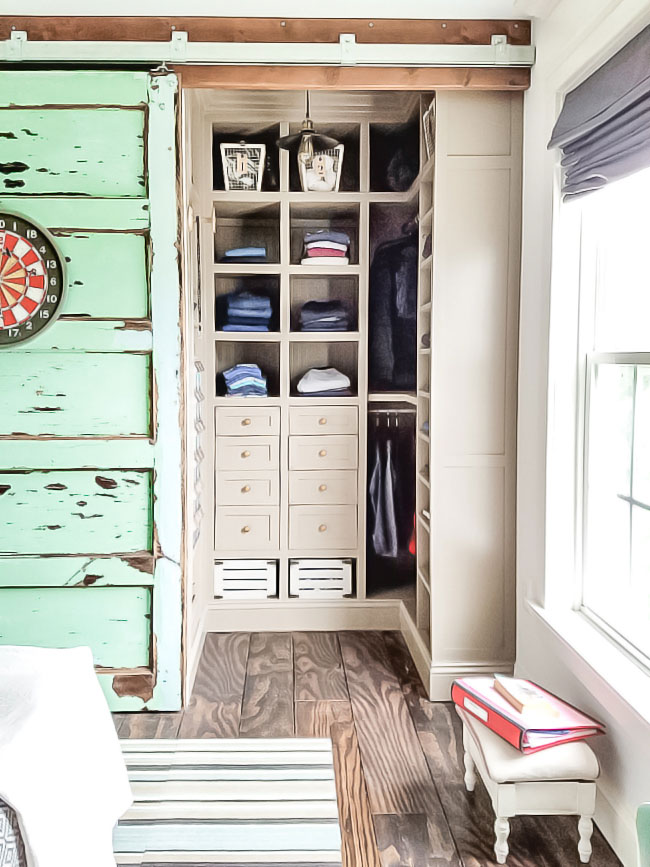 small closet makeover with lots of storage space, sliding door, vintage door, little stool, plywood floors