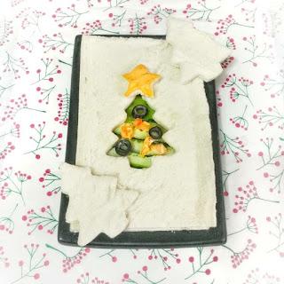 Pan de sándwich , con un árbol recortado de pan, en el huevo se ven lochas de pepino , círculos de aceituna y una estrella de queso