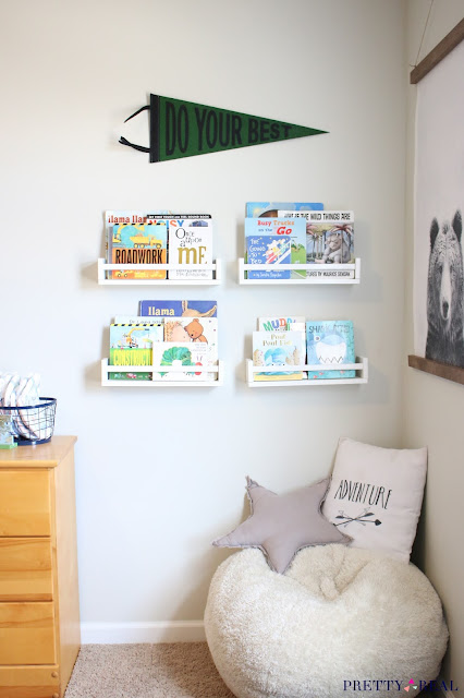 A cute reading nook with a bean bag for seating, fun art, wall mounted bookshelves