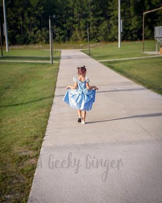 A little blonde girl in a blue cinderella dress, walking down the sidewalk through a field.