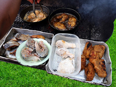 Fish and chicken cooking on the grill.