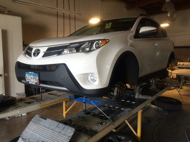 2015 Toyota RAV4 on frame rack being straightened after collision.