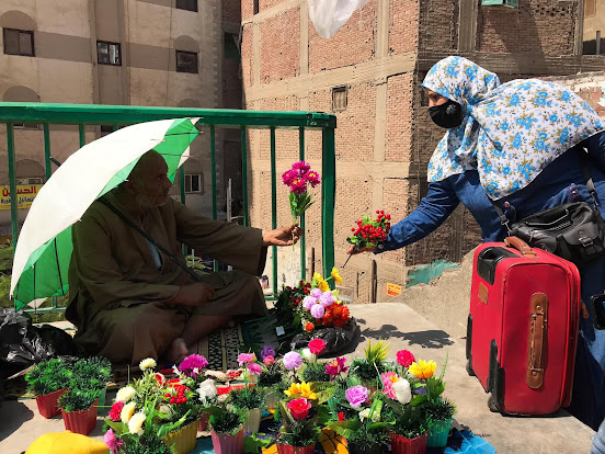 A masked lady buying plastic flowers in Giza from a street vendor  by Eslam Gomaa