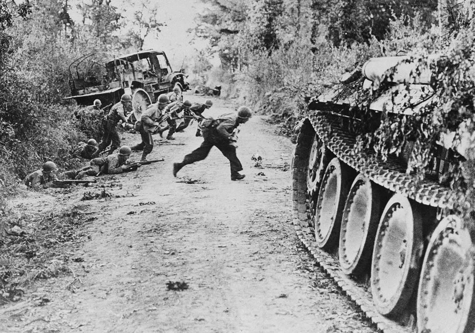 American soldiers race across a dirt road, which is under enemy fire, near St. Lo, in Normandy, France, on July 25, 1944. Others crouch in the ditch before making the crossing.