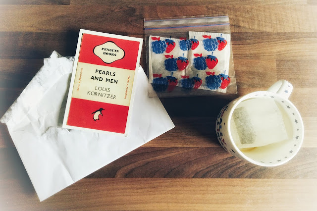 An opened envelope, a postcard of Penguin's Pearls and Men book, a bag of teabags, and a mug with a teabag in.